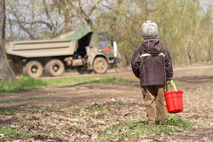 The little boy with a red children's bucket. Looks at passing big truck Royalty Free Stock Images