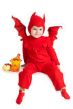 Little boy in red devil costume sitting with pumpkins Royalty Free Stock Photos