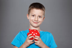 Little boy with red dotted piggy bank Royalty Free Stock Photo