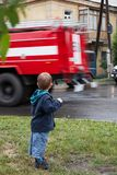 Little boy, red fire truck on road Stock Images