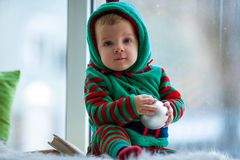 Little boy with ball sits on background of window. stock image