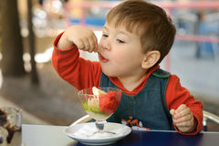 Little boy in a red hoodie eats ice cream Stock Photos