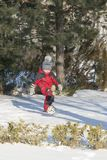 Little boy in red outfit playing happily over the snow. Little boy playing in the snow with a ball Stock Photography