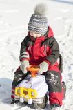 Little boy in red outfit playing happily over the snow. He boy is happy to see the snow ,he is standing on his knees with his hands up and playing with his toys Stock Photo