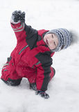 Little boy in red outfit playing happily over the snow Royalty Free Stock Photo