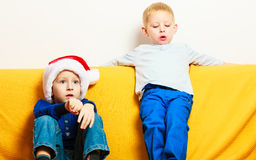 Little boy in red santa hat with his brother at home Royalty Free Stock Photography