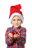 Little boy in red Santa hat with shiny Christmas balls Stock Photos