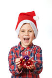 Little boy in red Santa hat with shiny Christmas balls Royalty Free Stock Images