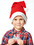 Little boy in red Santa hat with snowflake Stock Images