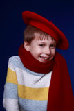 Little boy in red scarf and beret smiling. On blue background Stock Image