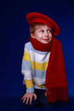 Little boy in red scarf and beret smiling. On blue background Stock Photo