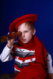 Little boy in red scarf and beret with a spyglass. Little boy in red scarf and beret looking into a spyglass on blue background Royalty Free Stock Photo