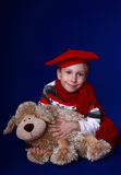 Little boy in red scarf and beret with a toy. Little boy in red scarf and beret smiling on blue background Royalty Free Stock Images