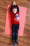 Little boy in a red shirt is laying on  a mat , doing exercise Royalty Free Stock Image