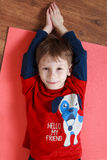 Little boy in a red shirt is laying on  a mat , doing exercise Stock Images