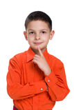 Little boy in a red shirt thinks. A cute little boy in a red shirt thinks on the white background Royalty Free Stock Photo