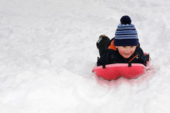 Little boy on red sled Royalty Free Stock Images
