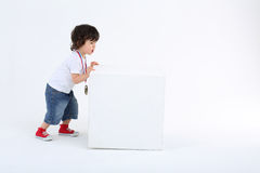 Little boy in red sneakers pushes large white cube Royalty Free Stock Photo