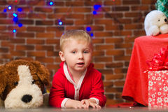 Little boy in red with soft toy dog. Little boy in red with big soft toy dog in christmastime indoors Stock Photo