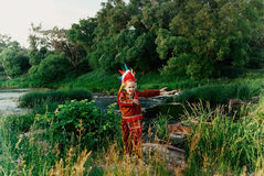 Little boy in  red suit Indian standing by the river with threshold and happily waving his arms Royalty Free Stock Images