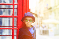 Little boy with red telephone box in the city Royalty Free Stock Photos