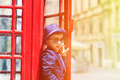 Little boy with red telephone box in the city Stock Image