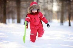 Little boy in red winter clothes having fun with fresh snow Royalty Free Stock Photos