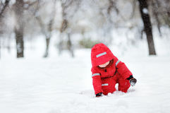 Little boy in red winter clothes having fun with snow during snowfall Royalty Free Stock Photography