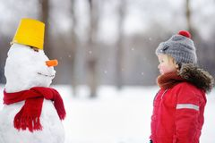 Little boy in red winter clothes having fun with snowman Stock Images