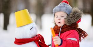 Little boy in red winter clothes having fun with snowman in snowy park royalty free stock images