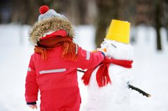 Little boy in red winter clothes having fun with snowman in snowy park Royalty Free Stock Photo