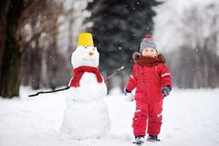 Little boy in red winter clothes having fun with snowman in winter park royalty free stock photos