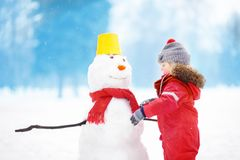 Little boy in red winter clothes having fun with snowman in snowy park Stock Photo