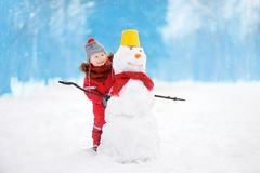 Little boy in red winter clothes having fun with snowman in snowy park Stock Image
