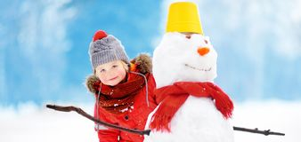 Little boy in red winter clothes having fun with snowman in snowy park stock photos
