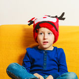 Little boy in red winter reindeer hat at home Stock Photos