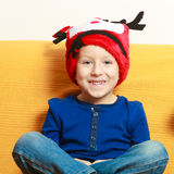 Little boy in red winter reindeer hat at home Stock Images
