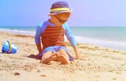 Little boy relax at summer beach, focus on feet Stock Images
