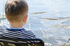 Little boy relaxing fishing at a lake. With a rod and reel, view from behind his head to the water and rod Royalty Free Stock Photography