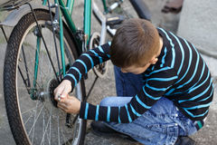 Little boy repairing bicycle outdoor Royalty Free Stock Photos