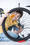 Little boy repairing bicycle tire in studio Stock Photos