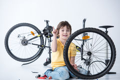 Little boy repairing bicycle tire in studio Royalty Free Stock Photo