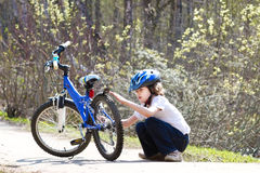 Little boy repairing his bicycle in a summer park Stock Photo
