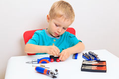 Little boy repairing toy train Royalty Free Stock Photos