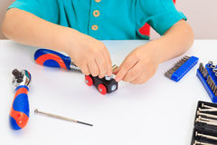 Little boy repairing toy train Stock Image