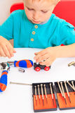 Little boy repairing toy train Royalty Free Stock Photography