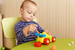 Little boy repairs auto Stock Images