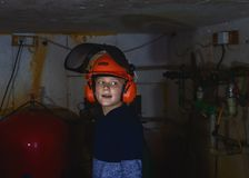 Little boy repairs water boilers in basement stock photography