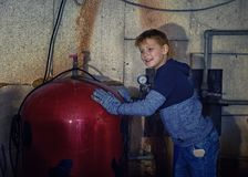 Little boy repairs water boilers in basement royalty free stock image