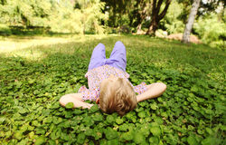 Little boy rest on the green park meadow. Carefree little boy lying on the green park meadow Royalty Free Stock Photo